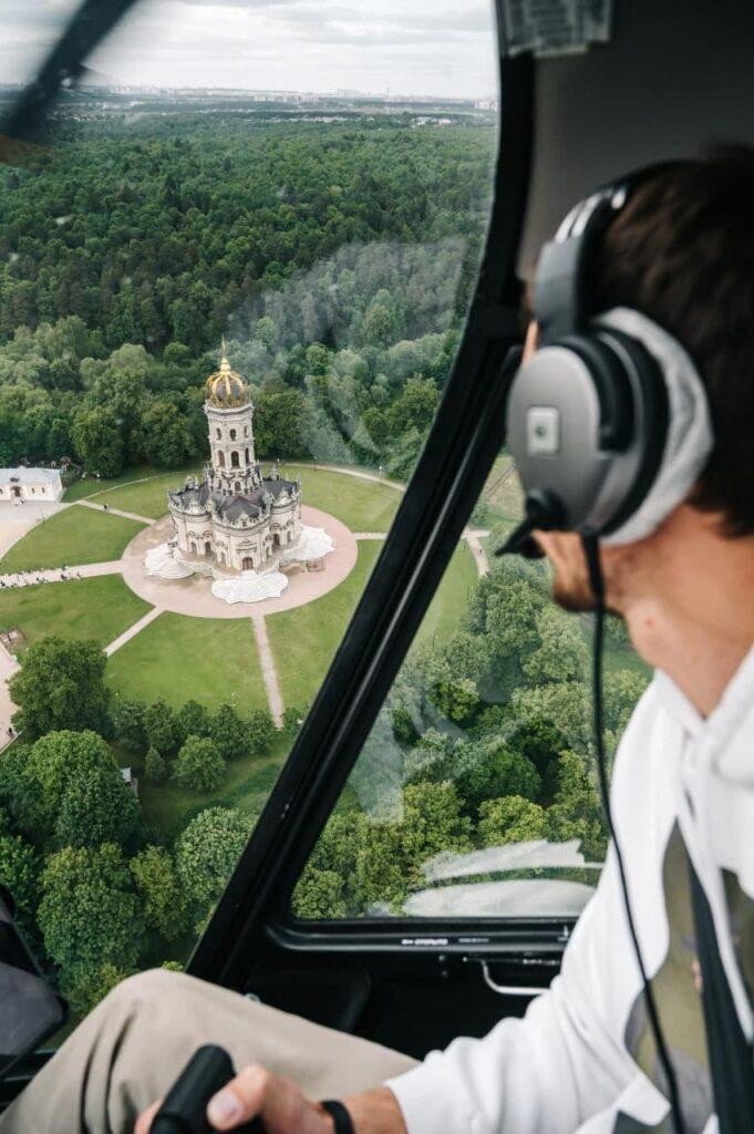 """Пилот вертолета на фоне Храма в Дубровицах при полете от компании """"Captour"""""""