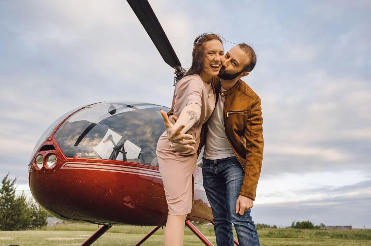 """Пара на фоне красного вертолета после прогулки от компании """"Captour"""""""