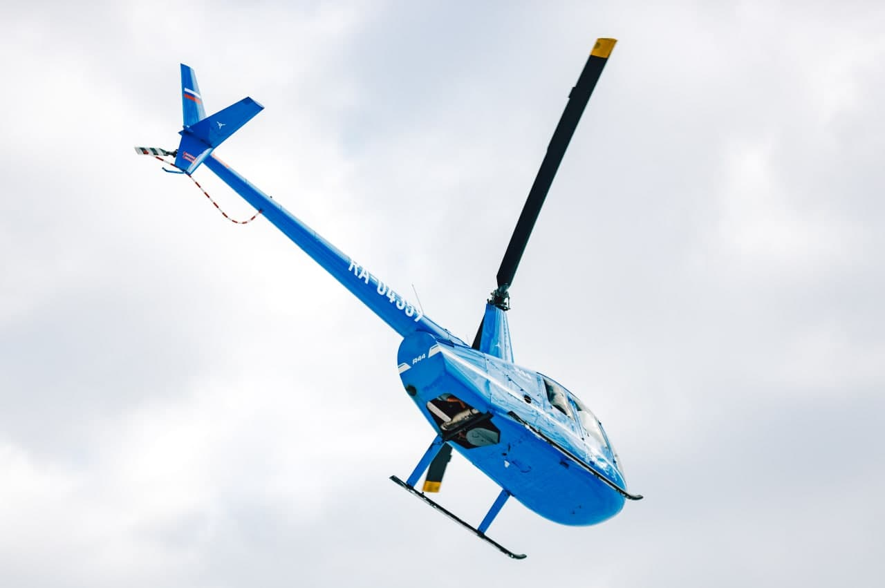 "Синий вертолёт Robinson R44 в небе в полете от компании ""Captour"""