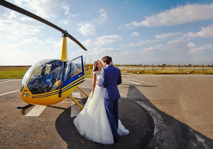 Поцелуй молодоженов на фоне вертолета