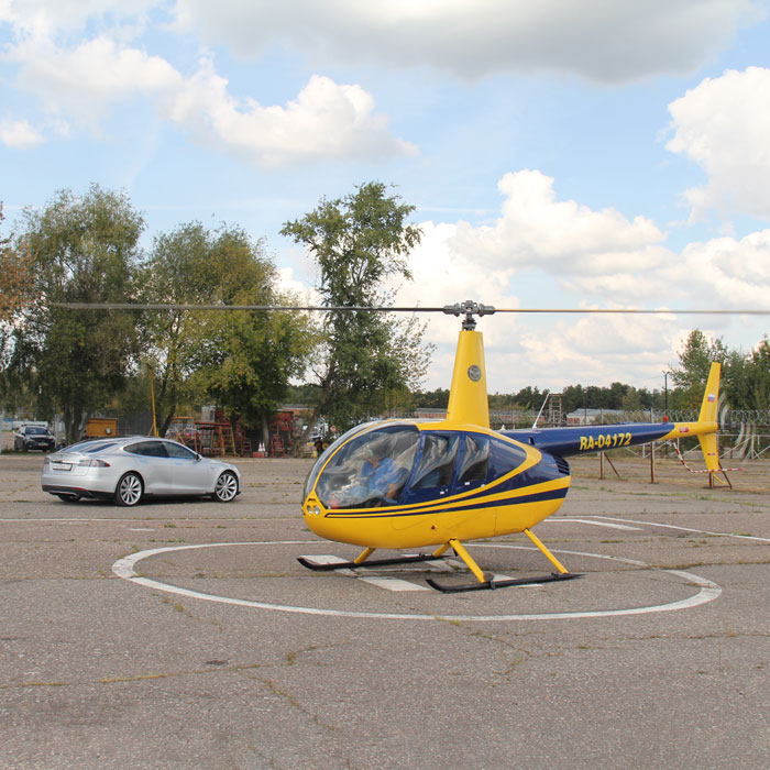 Вертолет и машина Tesla на вертолетной площадке в Мячково
