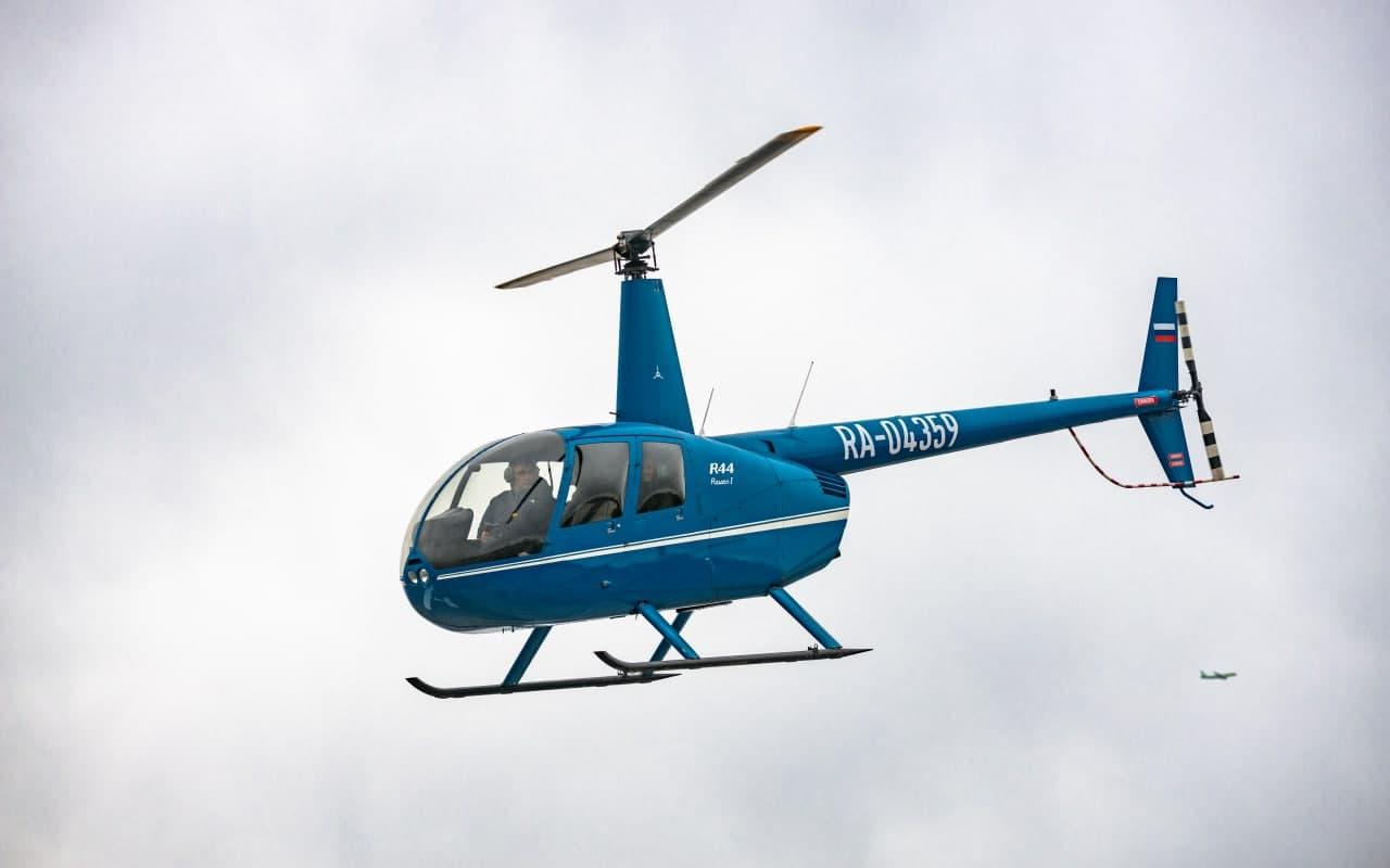 """Синий вертолёт Robinson R44 в небе от компании """"Captour"""""""