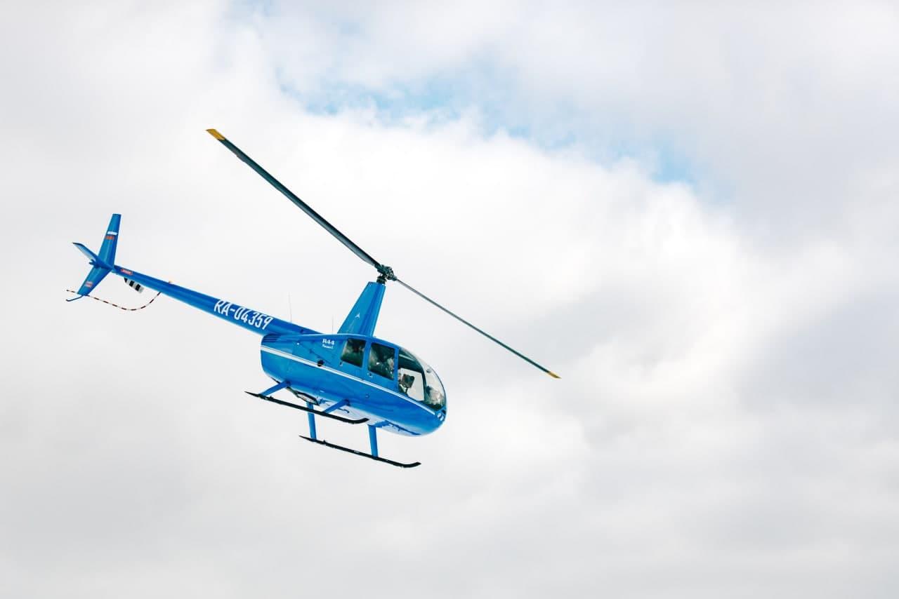 """Синий вертолет в небе от компании """"Captour"""""""