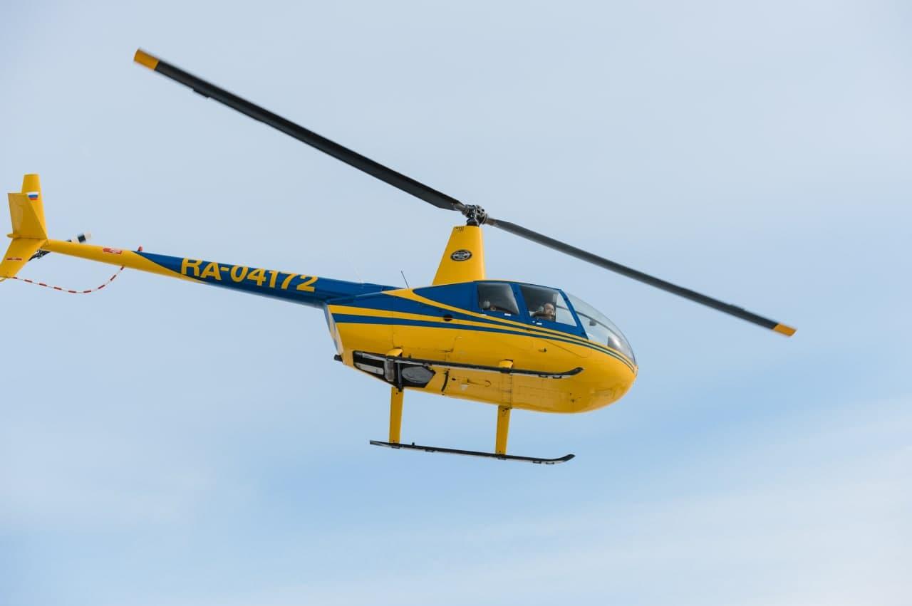 """Вертолёт Robinson R44 в небе в полете от компании """"Captour"""""""