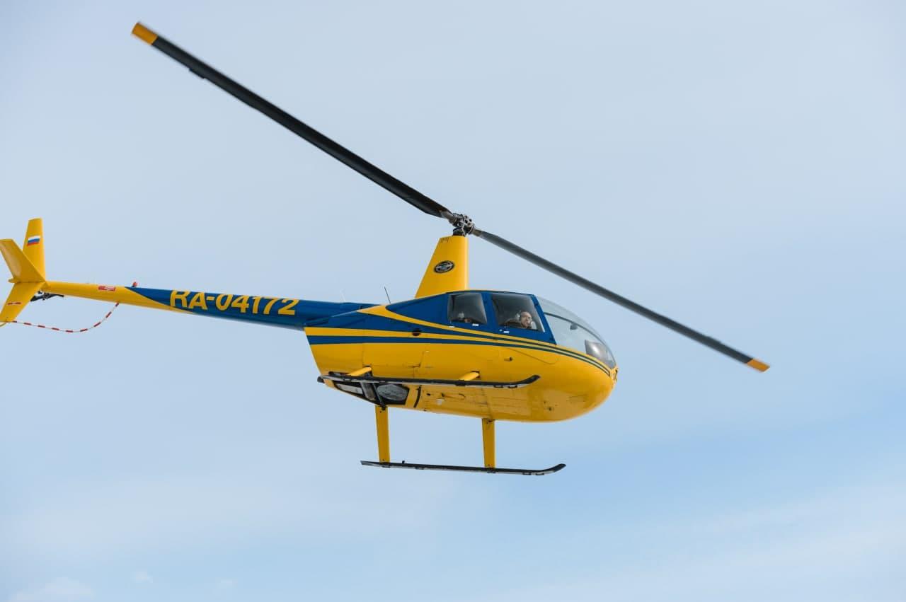 """Желтый вертолёт Robinson R44 в полёте от компании """"Captour"""""""