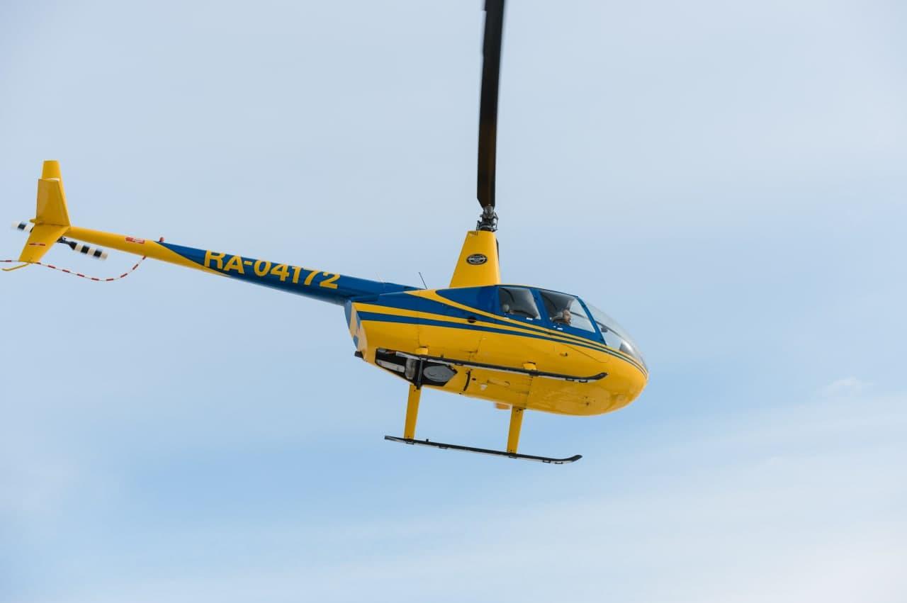"""Желтый Robinson R44 в полете от компании """"Captour"""""""